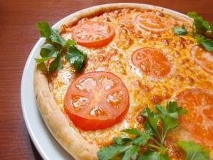 Pizza con rodajas de tomate y perejil