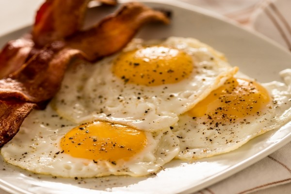 Un rico desayuno con tocino y huevos fritos