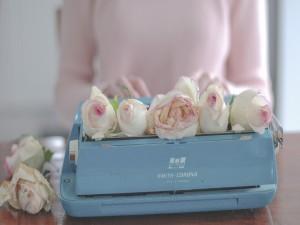 Delicadas rosas sobre una máquina de escribir