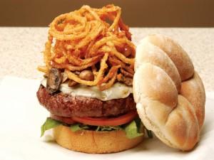 Aros de cebolla y champiñones sobre una hamburguesa