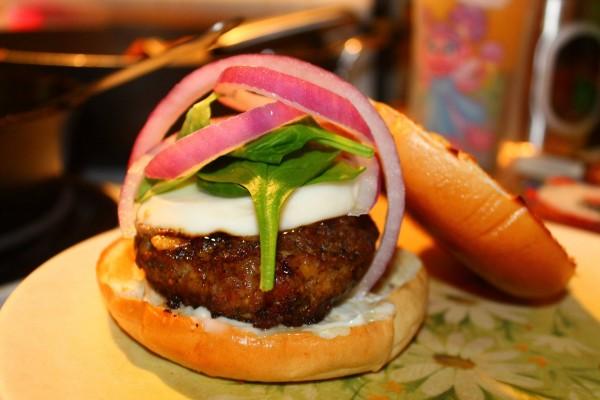 Hamburguesa con queso, cebolla morada y espinacas