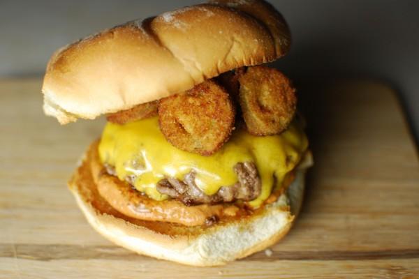 Pepino frito sobre una hamburguesa con queso