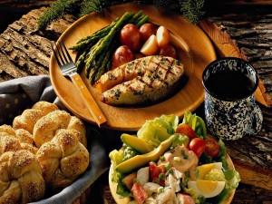 Plato con pescado, una ensalada y una cesta de pan