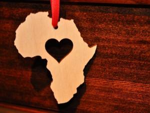 Postal: El continente africano tallado en una madera con un corazón