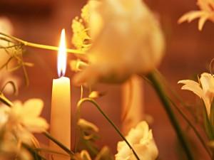 Postal: Una vela blanca rodeada de flores