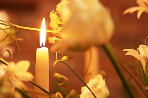 Una vela blanca rodeada de flores