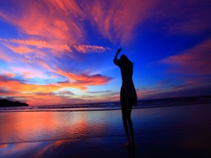 Postal: Una chica en la playa con los últimos rayos de sol