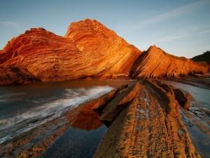 Los últimos rayos de sol iluminan las rocas y el agua