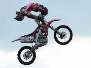 Postal: Piloto de motocross realizando un salto