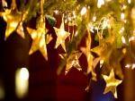 Estrellas doradas y luces en el árbol de Navidad