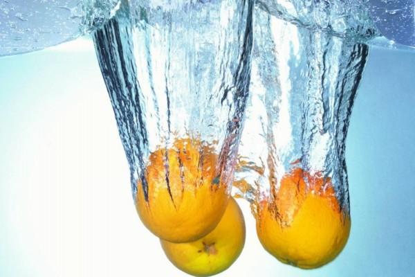 Tres naranjas cayendo al agua