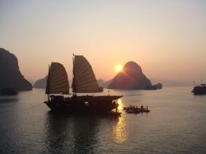 Postal: Barcos navegando al atardecer en la bahía de Ha Long