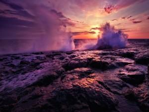 Olas chocando contra las rocas a la salida del sol