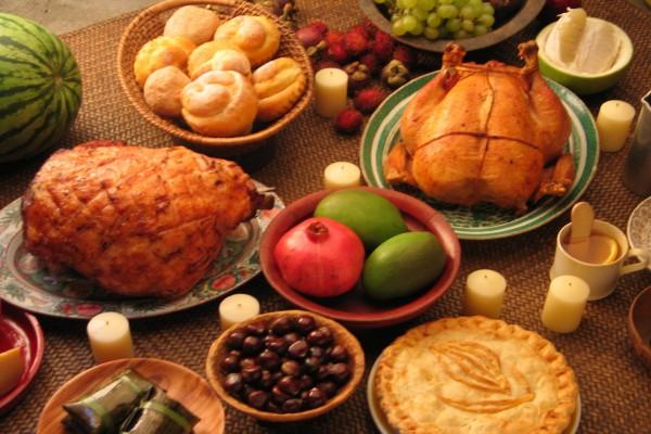 Velas en una mesa con asados, frutas y dulces
