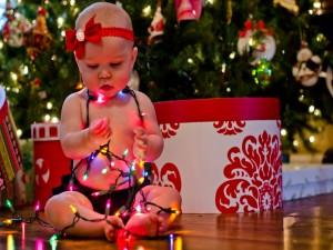 Una bebé cubierta de luces de Navidad