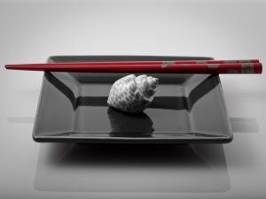 Postal: Caracola en un plato con palillos chinos
