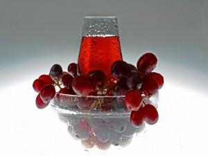 Uvas junto a un vaso con jugo de uvas