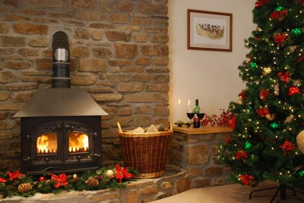 Chimenea encendida y copas de vino para celebrar la Navidad