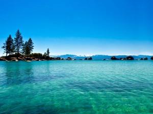 Postal: Isla rodeada de aguas turquesas y cristalinas