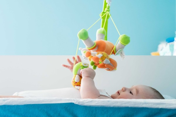 Un bebé jugando en su cuna