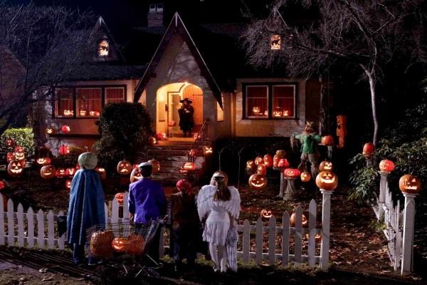 Niños junto a una casa en la noche de Halloween