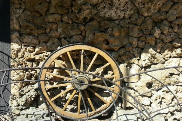 Rueda de madera junto a una pared de piedra