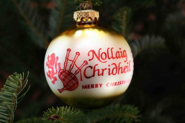 """""""Feliz Navidad"""" escrito en una bola colgada del árbol"""