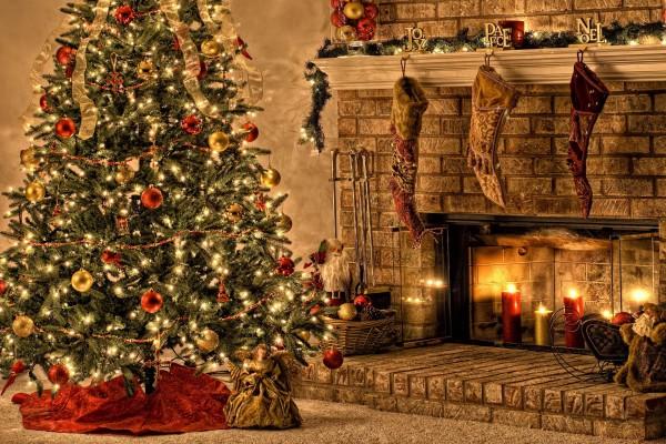 Árbol de Navidad junto a una gran chimenea con velas encendidas