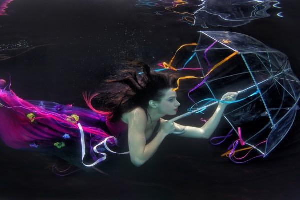 Una mujer bajo el agua con un paraguas