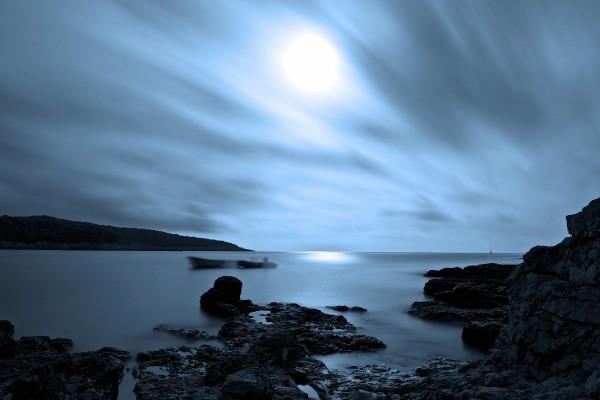 La luna entre las nubes iluminando el cielo y el mar