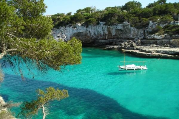 Embarcación en una cala de aguas cristalinas