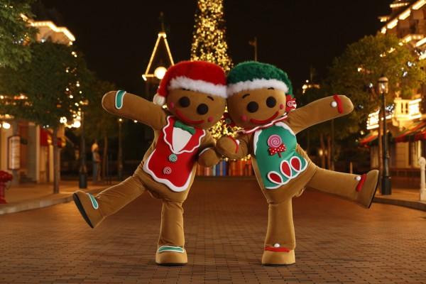 Dos hombrecillos de jengibre bailando en una calle el día de Navidad