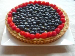 Un tarta de crema pastelera cubierta de arándanos y frambuesas