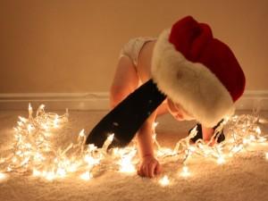 Un bebé tocando las luces de Navidad