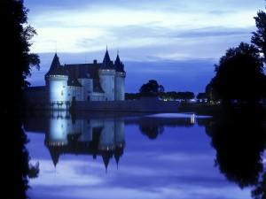 Postal: Castillo reflejado en el agua al anochecer