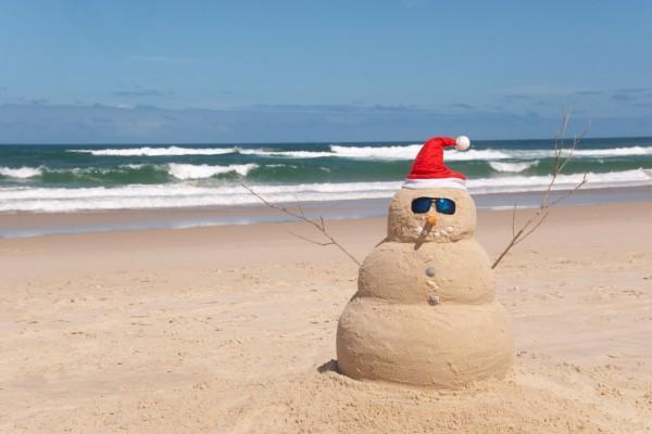 Muñeco navideño de arena en una playa