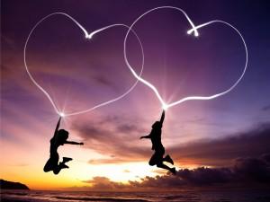 Pareja saltando en la playa con dos corazones