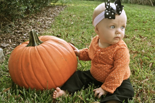 Una bebita junto a una calabaza