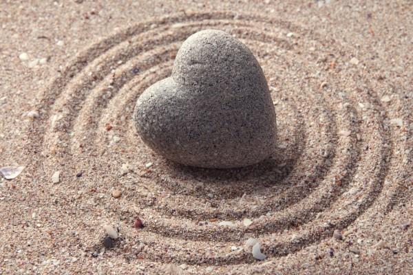Piedra corazón sobre la arena