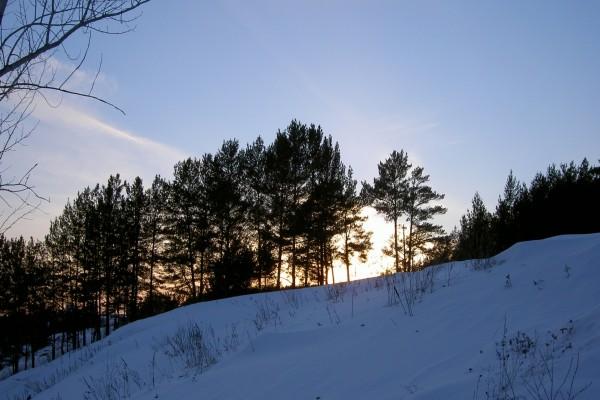 El sol tras la colina cubierta de nieve
