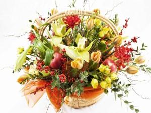 Un arreglo floral otoñal en una cesta de mimbre