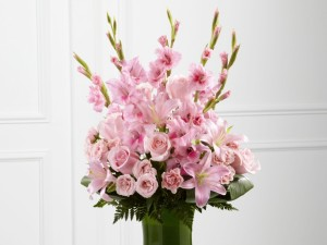 Postal: Gladiolos, lilium, rosas y eustomas de un bonito color rosa en un recipiente