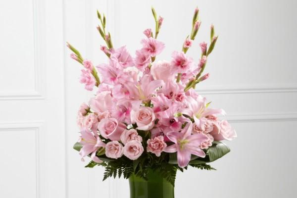 Gladiolos, lilium, rosas y eustomas de un bonito color rosa en un recipiente