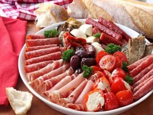 Barra de pan junto a un plato con fiambres y verduras