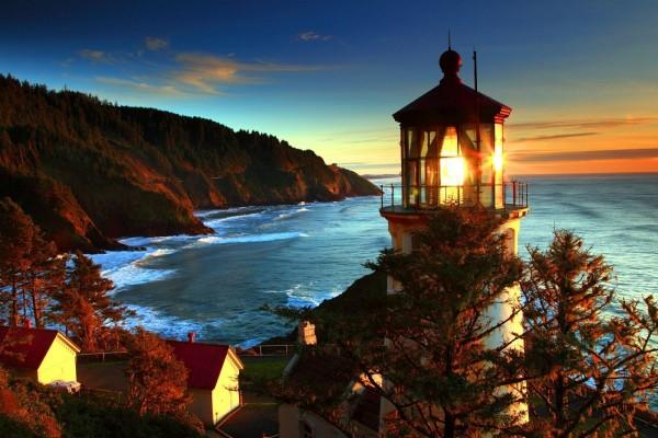 Un faro iluminado junto al mar y los acantilados