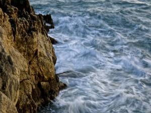 Postal: Olas chocando contra las rocas del acantilado