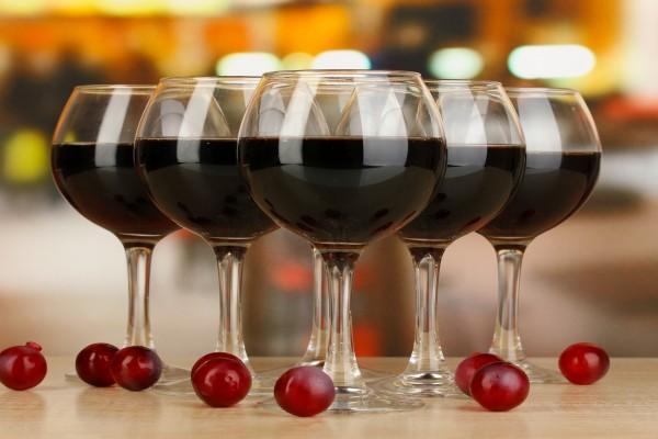 Copas con vino tinto y uvas sobre la mesa