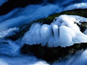 Hielo sobre una roca en el cauce del río