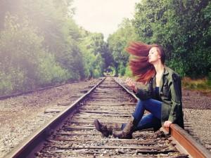 Una joven sentada en la vía del tren