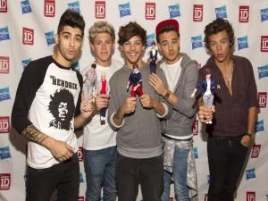 Los chicos de One Direction mostrando sus muñecos